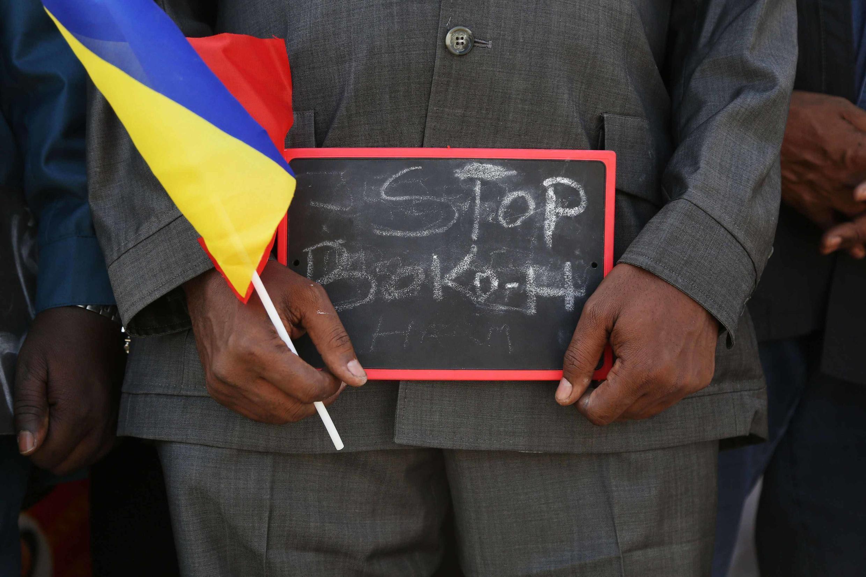 Homem mostra cartaz pedindo o fim da ação do Boko Haram durante a chegada das tropas do Chade em Camarões.