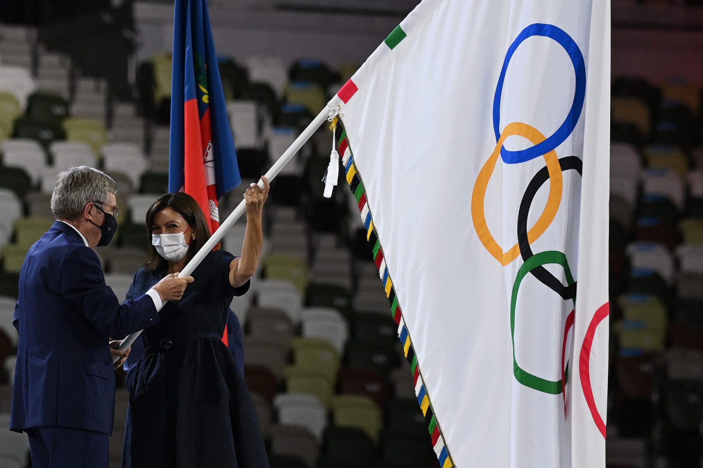 L'Allemand Thomas Bach, président du Comité International Olympique, remet le drapeau olympique à la maire de Paris, Anne Hidalgo, le 8 août 2021 lors des Jeux Olympiques de Tokyo 2020