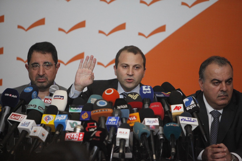 O ministro libanês da Energia, Gebran Bassil (centro), aliado do Hezbollah, anuncia sua demissão durante coletiva em Rabieh, no Líbano.
