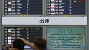 Giá cổ phiếu của Malaysia Airlines sụt gần 20% sau tai nạn xảy ra. Bên cạnh là bảng thông báo kêu gọi cầu nguyện cho các nạn nhân MH17.