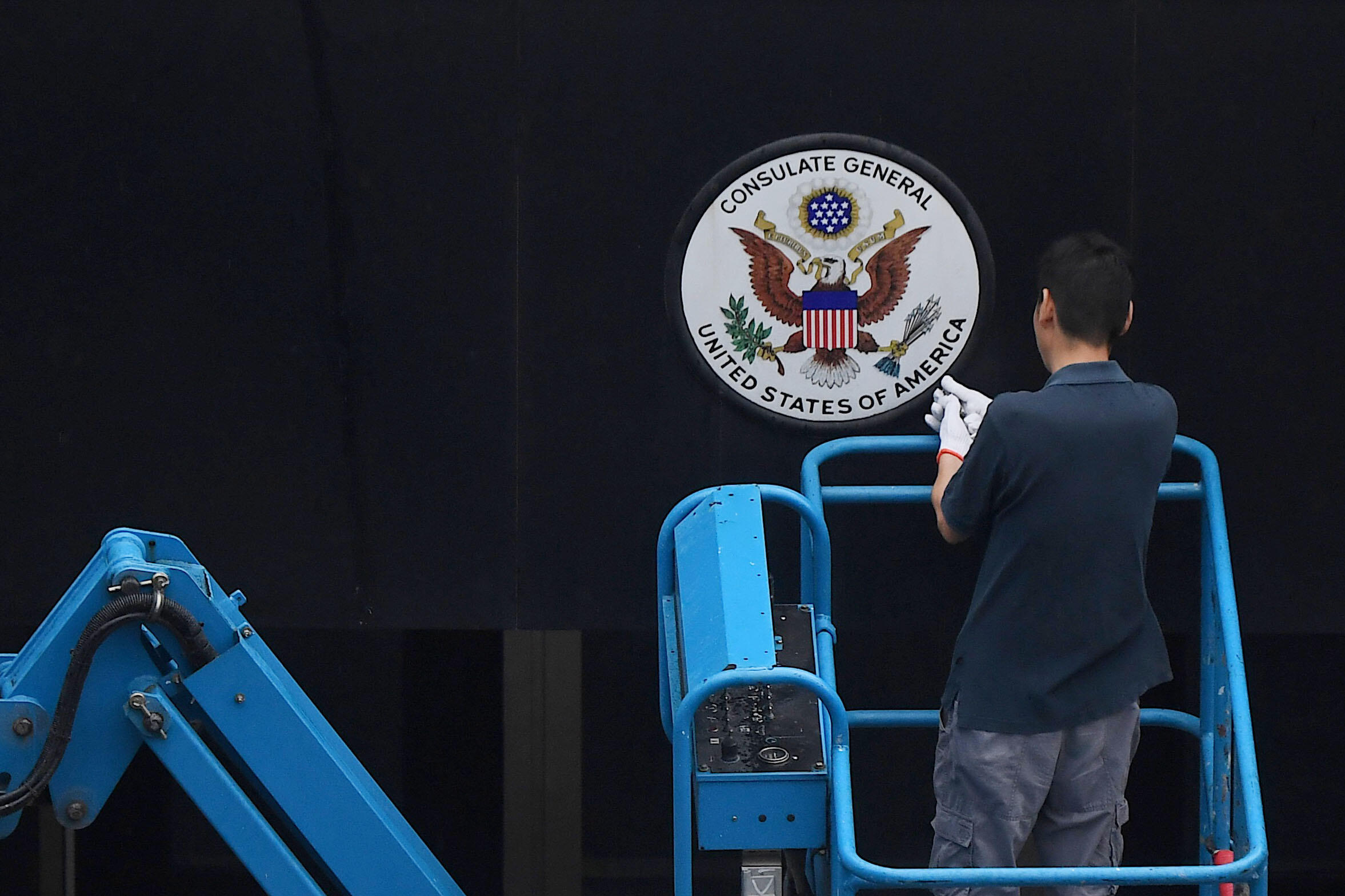 Un trabajador chino retirando la insignia nacional de Estados Unidos del edificio del consulado en Chengdu, suroeste de China.