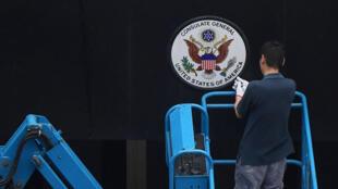 Un travailleur enlève le panneau à l'entrée du consulat américain à Chengdu, dans la province du Sichuan, le 25 juillet 2020.