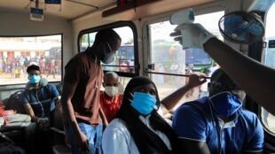 Un agent sanitaire prend la température des passagers d'un bus à Dakar le 28 mai 2020.