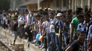 Migrantes esperam por trem em uma estação da Macedônia para tentar chegar à Sérvia.