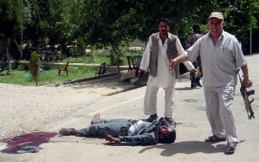 Le personnel de sécurité signale une des victimes de l'attentat suicide, le 17 mai 2012, dans la province de Farah en Afghanistan.