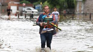 Un hombre camina con pertenencias en uns calle inundada de Angleur, cerca de la ciudad belga de Lieja, el 16 de julio de 2021