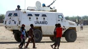 Wasu kananan yara 'yan Sudan a kusa da motar sulken sojojin Majalisar Dinkin Duniya UNAMID a birnin Nyala, dake yankin Darfur.