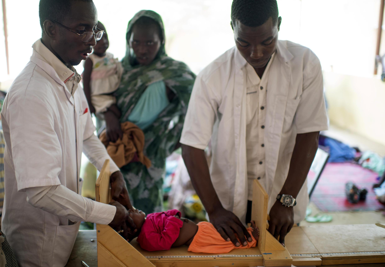 Des médecins auscultent un enfant et prodiguent à la mère des conseils préventifs pour éviter la malnutrition, dans la région de Tombouctou, le 5 octobre 2017.