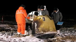Researchers work next to Chang'e-5 lunar return capsule carrying moon samples, after it landed in northern China.