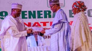 Shugaban Najeriya Muhammadu Buhari lokacin da ya ke karbar shaidar nasararsa a zaben kasar na 2019 a hannun sugaban hukumar INEC Farfesa Mahmood Yakubu