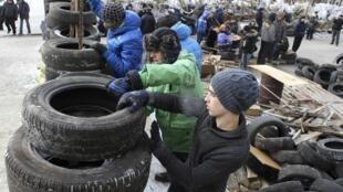 A Lviv, des manifestants construisent des barricades faites de pneus et de bois de récupération.