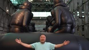 Ai Weiwei à Sydney en 2018 devant sa sculpture « Law of the Journey 2017 » qui décrit le quotidien des réfugiés migrants.