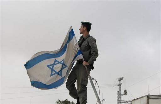 Một người lính Israel treo cờ ở chốt kiểm soát Atarot gần Jerusalem (AFP / Ahmad Gharabli)