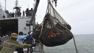 Equipes responsáveis pela investigação sobre a queda do voo QZ8501 supervisionam peças do avião resgatadas no mar de Java.