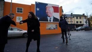 Le président-élu Joe Biden a toujours mis en avant ses racines irlandaises. Ici, sa cousine irlandaise lointaine, Laurita Blewitt, pose devant une fresque en son hommage, à Ballina, le 28 octobre 2020.