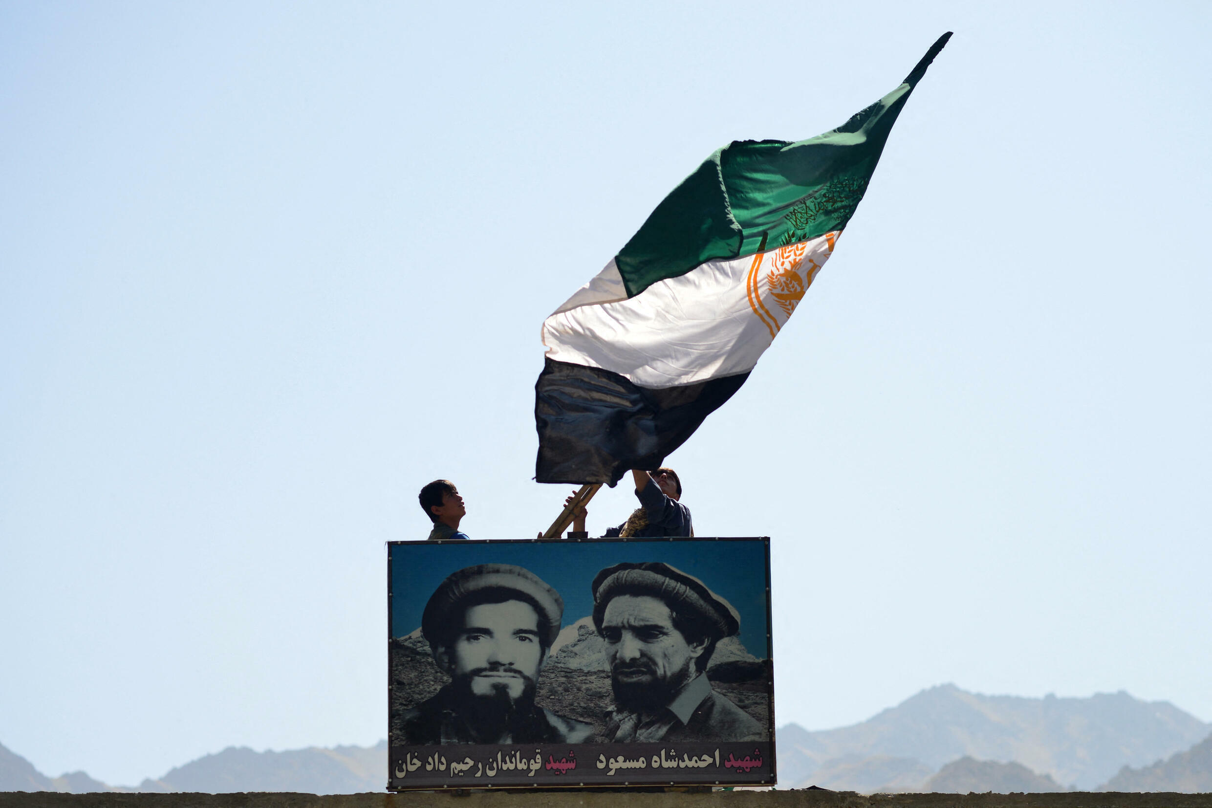 Afghan men wave a flag above the portrait of late Afghan commander Ahmad Shah Massoud (R) in Paryan district of Panjshir province on August 23, 2021, as the Taliban said their fighters had surrounded resistance forces holed up in the valley, but were looking to negotiate rather than take the fight to them.