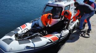 Guarda costeira turca e voluntários carregam corpos de refugiados e migrantes após naufrágio.
