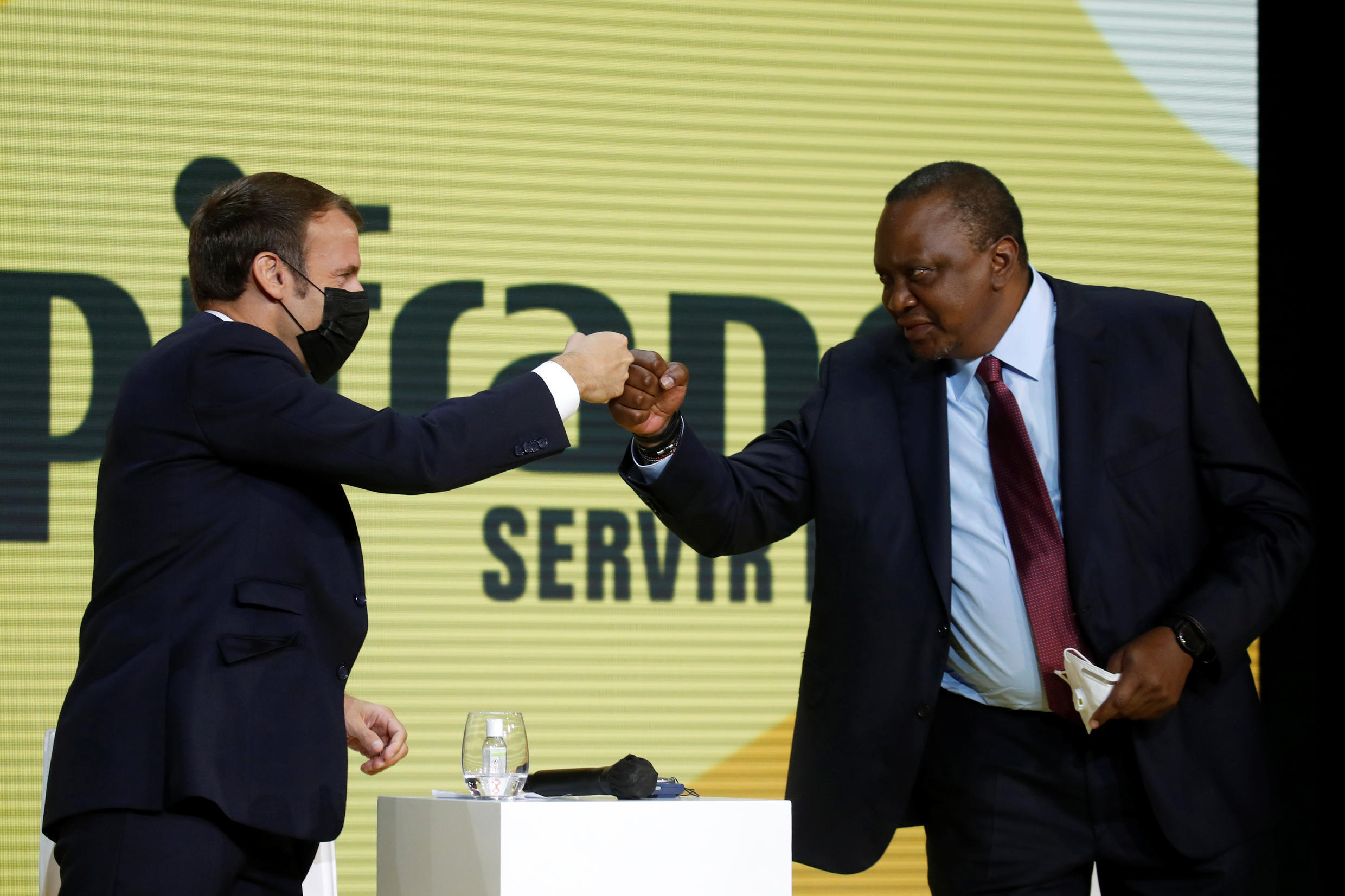 """French President Emmanuel Macron and Kenya's President Uhuru Kenyatta fist bumps at the annual tech conference """"Inno Generation""""organized by French investment bank Bpifrance in Paris, France, October 1, 2020."""