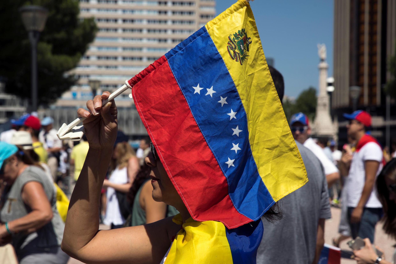 Женщина с флагом Венесуэлы во время референдума против президента страны Николаса Мадуро, 16 июля 2017.