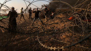 Des manifestants Palestiniens jettent des pierres en direction des troupes israéliennes, à la barrière entre Gaza et Israël, le 12 octobre 2018.