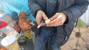 A Kurdish man prepares a meal with friends at the migrant camp in Grande-Synthe, near Dunkirk in northern France.