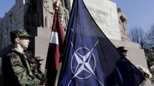 Một người lính tahi Riga cầm cờ NATO, nhân dịp Latvia gia nhập khối liên minh Bắc Đại Tây Dương - REUTERS /Ints Kalnins