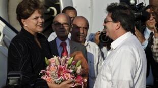 A presidente DIlma Rousseff recebe flores na sua chegada a Cuba.