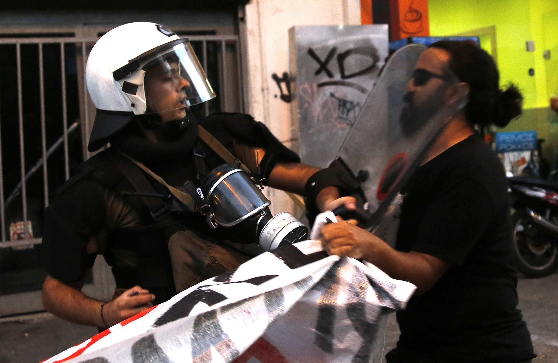 Un policier anti-émeute frappe un manifestant anti fasciste, lors de la marche organisée le 19 septembre, après l'assassinat de Pavlos Fyssas.