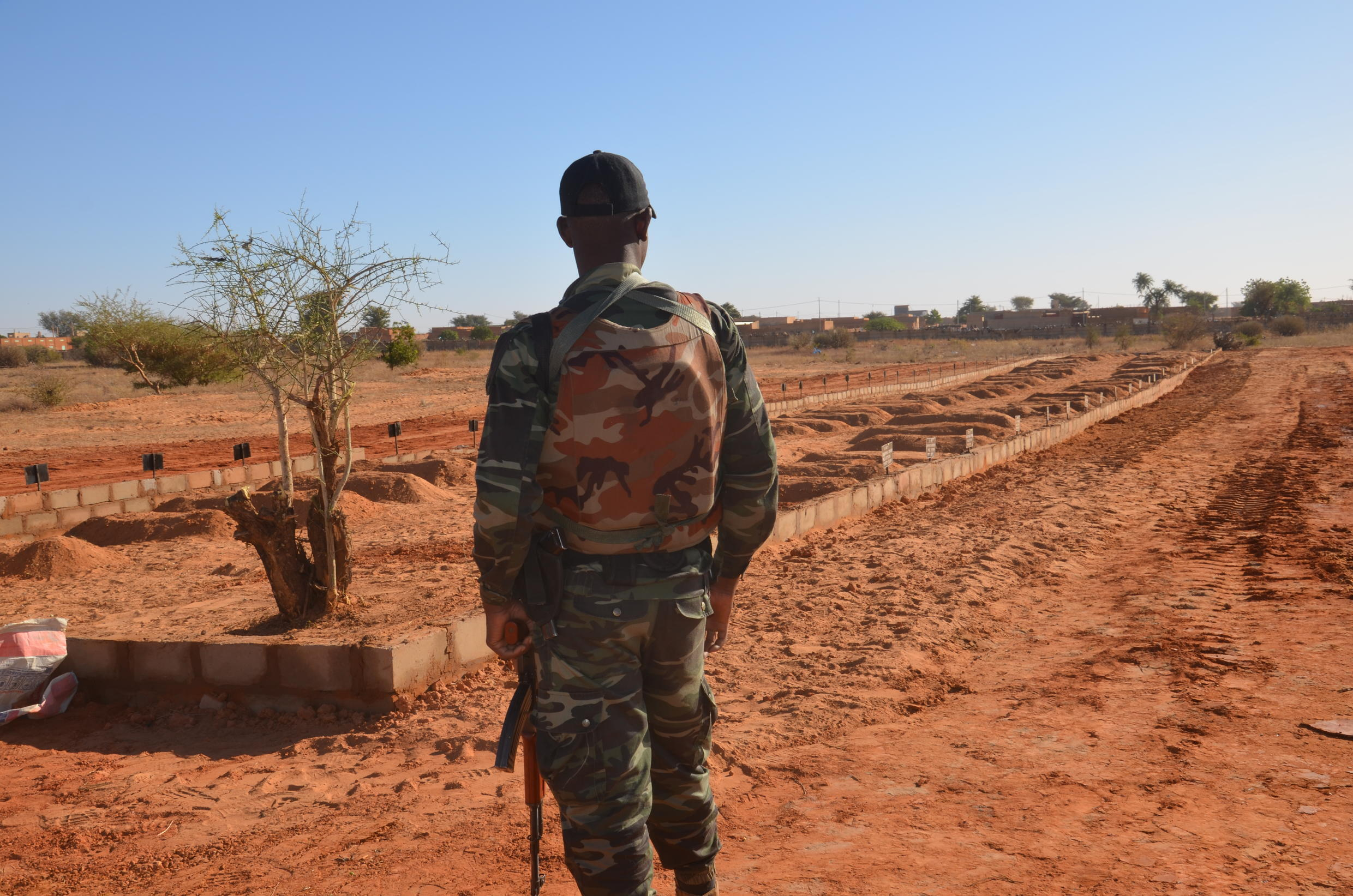 A Niger soldier looks at the graves of 71 Niger troops soldiers killed  in a jihadist attack on December 10, 2019, ahead of a regional summit to coordinate a response to the growing unrest.