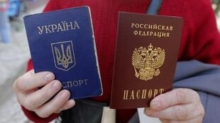 Một phụ nữ trương ra hai hộ chiếu, Ukraina, màu xanh và Nga, màu đỏ, mà bà vừa nhận được tại Simferopol ở Crimée. Ảnh tư liệu chụp ngày 07/04/2014.