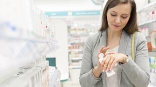 Une femme teste une crème dans une pharmacie.