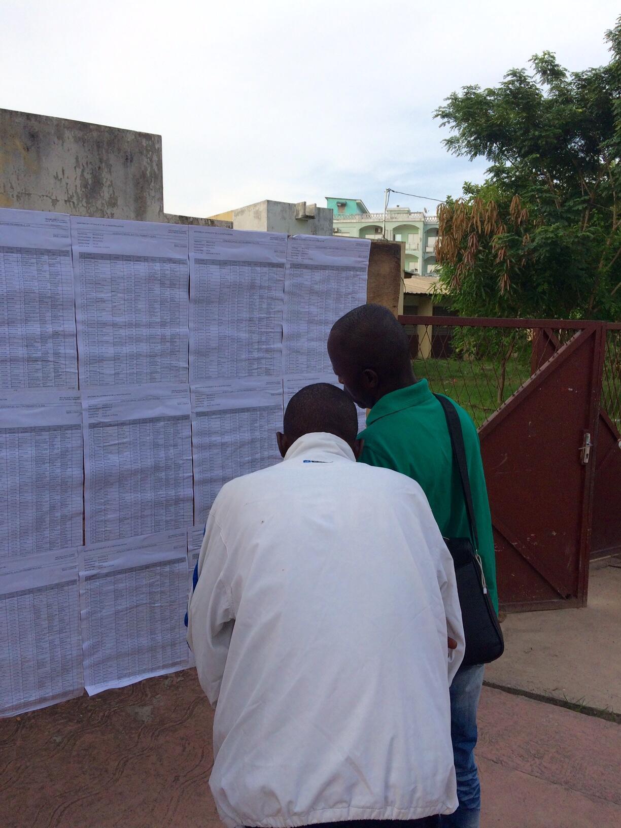Des électeurs consultent un panneau d'affichage devant un bureau de vote dans le quartier de Poto-Poto à Brazzaville, le 20 mars.