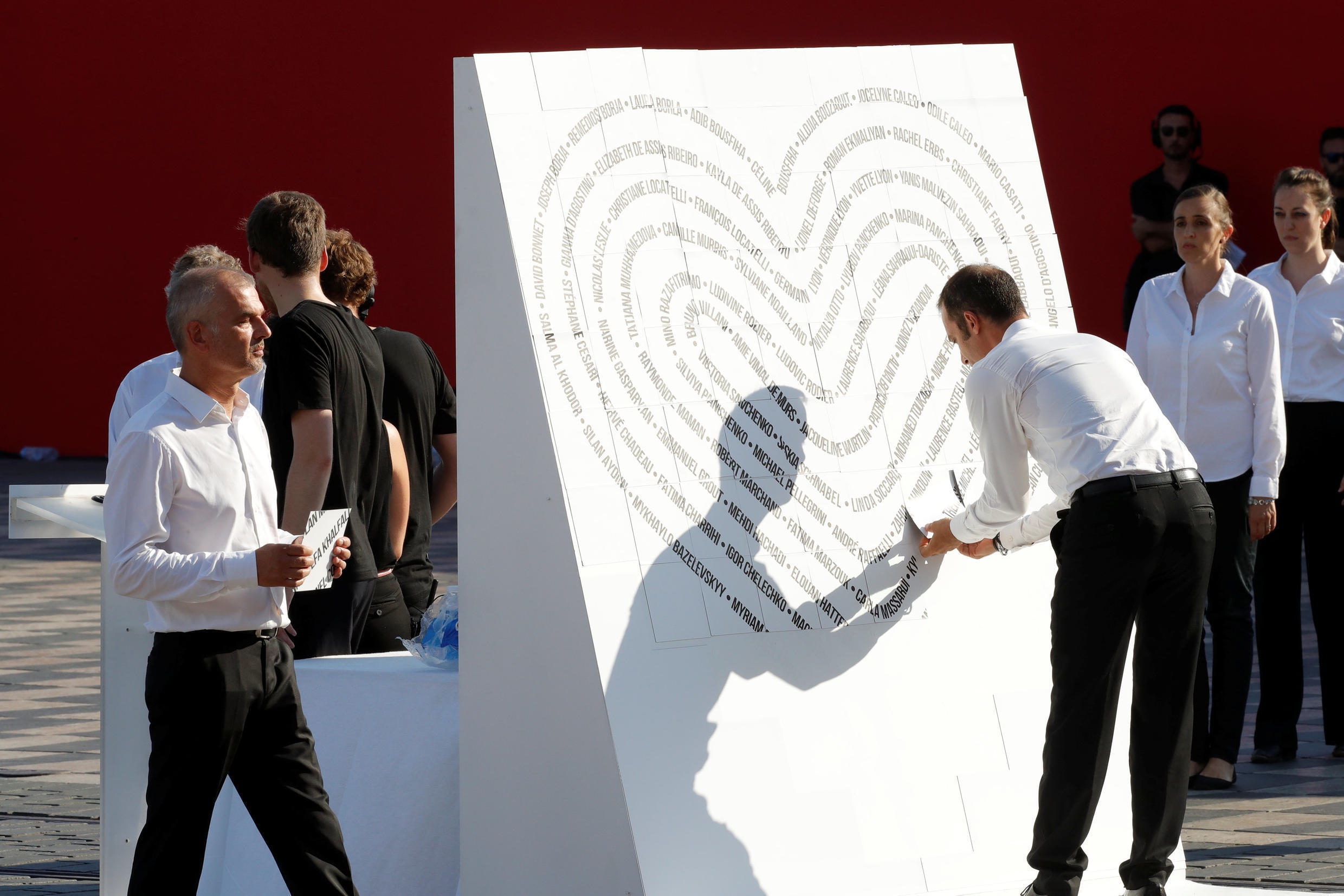 People stick the names of the 86 victims to form a heart during the commemorative ceremony for last year's July 14 Bastille Day fatal truck attack on the Promenade des Anglais in Nice, France, July 14, 2017.