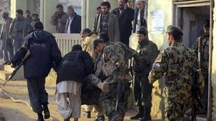 A wounded Afghan soldier is carried away from the battle in Kunduz