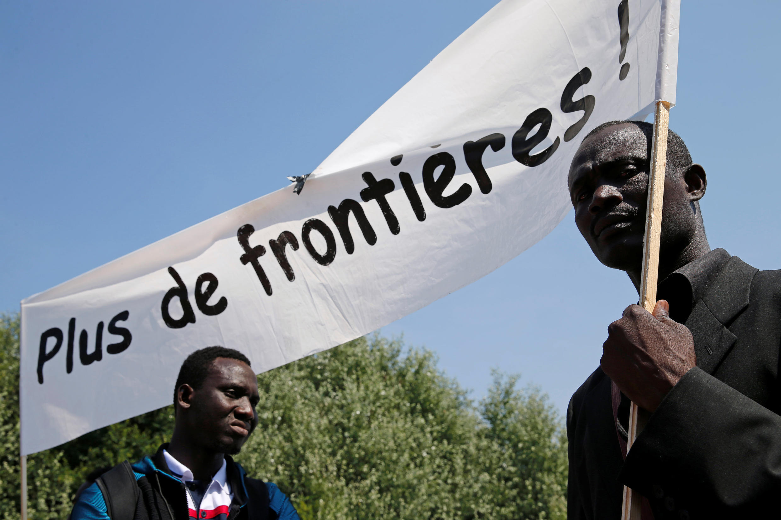 """Migrants holding a banner saying """"No more borders!"""" on a solidarity march in Calais on 7 July"""