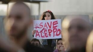 """""""Sauvez Alep"""" កុមារីឈរកាន់បដាសុំក្តីសង្គ្រោះក្រុងអាឡិប ក្នុងបាតុកម្មនៅក្រុងទីប៉ូលី កាលពីថ្ងៃទី ១ ឧសភា"""