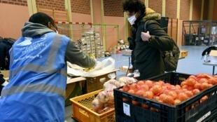 Un étudiant reçoit de la nourriture lors d'une distribution par l'association caritative du Secours Populaire, le 20 décembre 2020.
