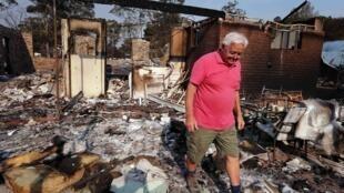 Um morador caminha entre os escombros de sua casa destruída em Winmalee, em 21de outubro de 2013.