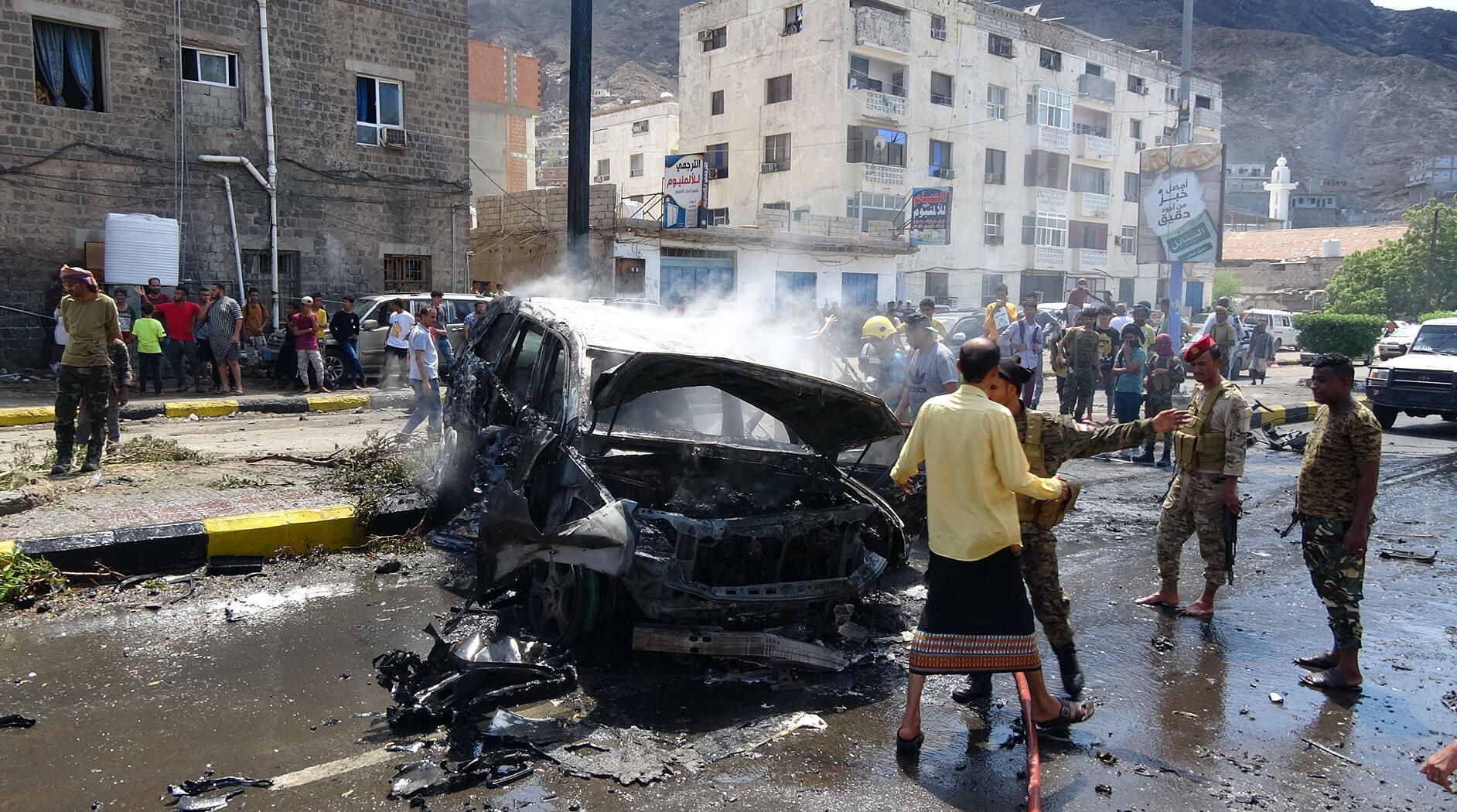 Yemeni security forces and onlookers gather at the scene of a car-bomb explosion in the heart of Yemen's southern port city of Aden on Sunday