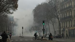 Teargas clouds the streets approaching Place de la Madeleine during Saturday's Yellow Vest protest