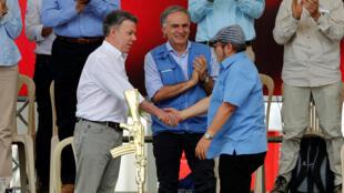 Apretón de manos entre Juan Manuel Santos y Rodrigo Londoño, este 27 de junio de 2017 en Mesetas, Colombia.