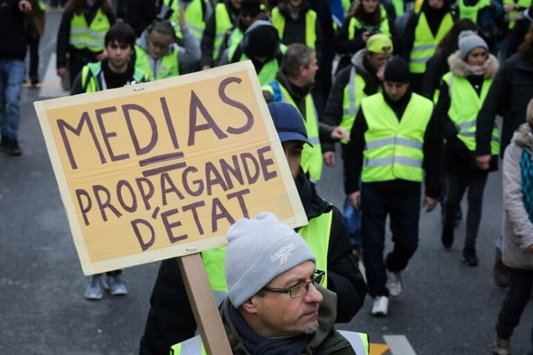 Media=state propaganda, reads a sign held by a Yellow Vest supporter in January 2019. Scepticism of the government and the media run deep in the movement, making some open to the QAnon conspiracy.