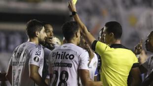 El árbitro colombiano Wilmar Roldan le muestra tarjeta amarilla al arquero del Santos John during en una foto tomada el 16 de diciembre de 2020 en duelo de Copa Libertadores ante Gremio en Brasil. El golero es uno de dos jugadores de Santos que dio positivo tras participar en duelo de semifinal de Libertadores ante Boca en Buenos Aires.