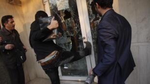Manifestante chuta porta da embaixada britânica, em Teerã, na terça-feira.