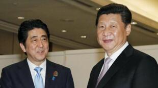 Poignée de main entre le président japonais Shinzo Abe (g) et son homologue chinois Xi Jinping. Jakarta, le 22 avril  2015.