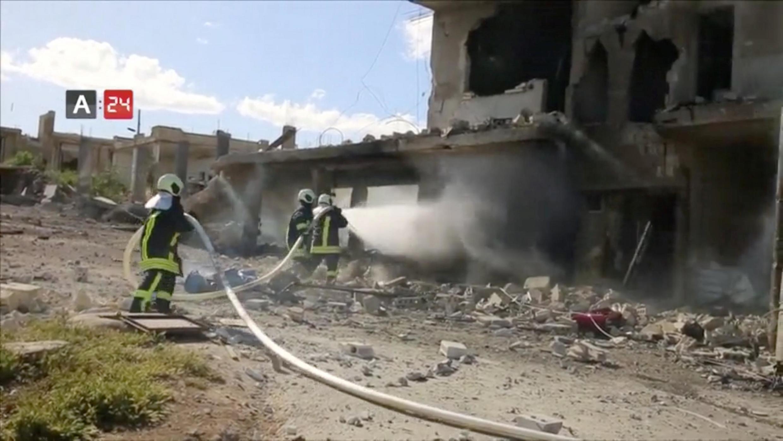 Пожарные тушат подвергшееся бомбардировке здание больницы в провинции Идлиб, Сирия, 6 мая 2019.