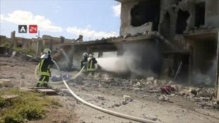 Firefighters respond at the destroyed building of Nabd Al-Hayat hospital that was hit by an air strike in Hass, Idlib province, 6 May 2019