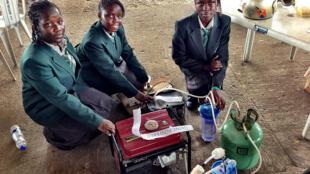 Trois jeunes filles présentent un générateur alimenté à l'urine lors de la foire des inventeurs 2012 : « Maker Faire Africa ».