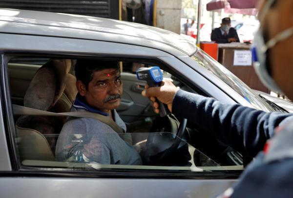 Contrôle de la température corporelle avec un thermomètre infrarouge à l'entrée d'un bureau à New Delhi, en Inde.