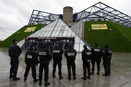 Policiais observam faixas do Greenpeace colocadas na entrada do ginásio de Paris Bercy.